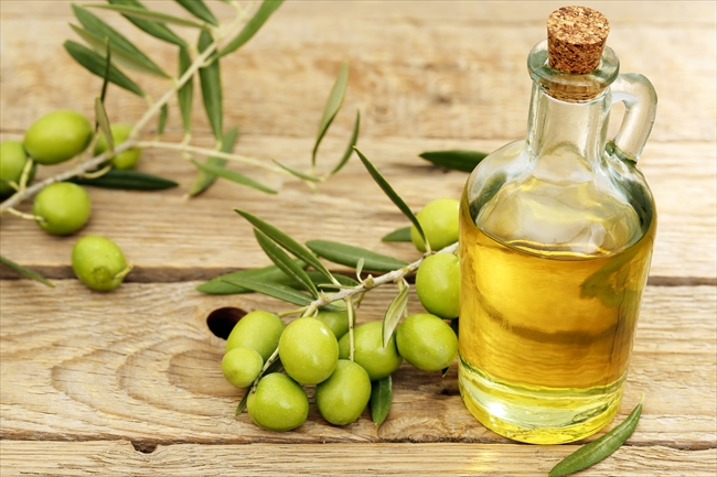 olive oil with branch of olive tree placed on wooden background