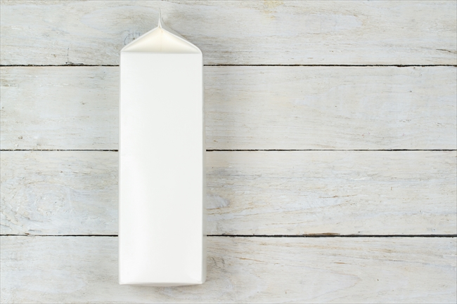 Blank cardboard milk pack on wooden table